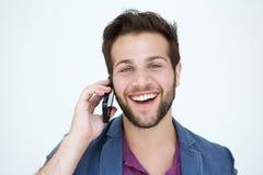 Kyla den unga mannen som ler med mobiltelefonen på vit bakgrund Royaltyfri Bild