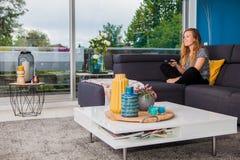 Kyla och hållande ögonen på tv för ung kvinna från soffan arkivfoto