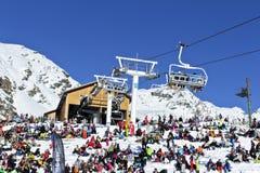 Kyla ut efter att ha skidat och snowboarding på en snöig lutning i höga fjällängar Arkivfoto