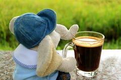 Kyla ut med en kopp kaffe, en elefantdocka med varmt kaffe på terrassen arkivbilder