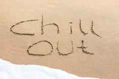 Kyla ut - skrivet i sanden fotografering för bildbyråer