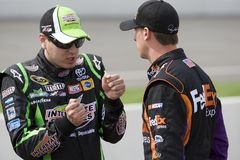 Kyle Busch talks with Denny Hamlin. BROOKLYN, MI - AUG 13, 2010:  Kyle Busch (18) talks with teammate Denny Hamlin (11) before qualifying for the Carfax 400 race Stock Images