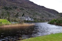 Kylemore Abbey Ireland Connemara on River. Grass mountain hill lake water green meadow castle house travel Stock Photography