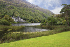 Kylemore Abbey in mountains on the lake. Royalty Free Stock Images