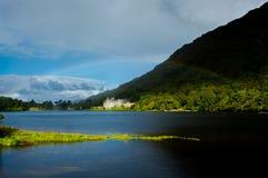 Kylemore-Abtei in Irland unter einem Regenbogen Stockfotos