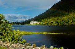 Kylemore-Abtei in Irland unter einem Regenbogen Stockbild