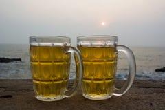 Kylt öl vid havet på solnedgången royaltyfria bilder