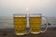 Kylt öl vid havet på solnedgången royaltyfri bild