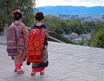 Kyoto. A very specific travel image for Kyoto,Japan:two geishas in front of Kyomizudera temple looking to the city with Kyoto Station Tower visible in the Stock Photos