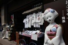 KYOTO, GIAPPONE - 23 LUGLIO 2016: La grande bambola davanti alle magliette è visualizzata ad un negozio di ricordo Immagine Stock
