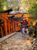 KYOTO, JAPÃO - 5 DE JULHO DE 2017: Mulher não identificada que levanta para a câmera em Tori Gate vermelha no santuário de Fushim Imagens de Stock Royalty Free