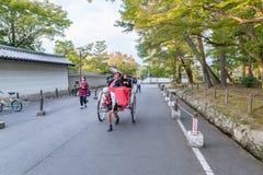 KYOTO, JAPÃO - 8 DE OUTUBRO DE 2015: Riquexó no Tóquio, Japão Com o parque local de Poople e de Shite no fundo foto de stock