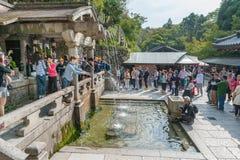 KYOTO, JAPÓN - 9 DE OCTUBRE DE 2015: El agua que espera de la gente para en alson del templo de la capilla de Kiyomizu-dera sabe  Imagen de archivo