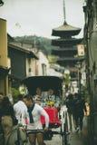 Kyoto Japón - november9,2018: ropa vieja del traditon del kimono de la mujer que lleva japonesa que se sienta en carrito en la ca fotos de archivo libres de regalías