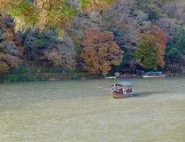 Kyoto Japón-noviembre 28,2016: El barco turístico tradicional pasa encendido el río esmeralda del katsura del color, Arashiyama,  Fotos de archivo libres de regalías