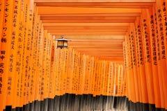 Kyoto, Jap?n - 27 de diciembre de 2009: T?nel de madera anaranjado del torii en la capilla de Fushimi Inari Taisha Es uno del lug fotografía de archivo libre de regalías