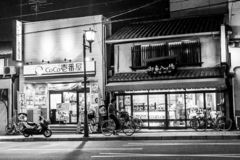 Kyoto, Japan - December 26, 2009: A man on a bicycle near the store on Gion street at night stock photo
