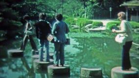 KYOTO JAPAN -1972: Folk som går klivastenarna runt om dammet för japansk stil för zen arkivfilmer