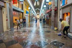 KYOTO, JAPAN - JULI 05, 2017: Niet geïdentificeerde mensen die met bezems buiteno schoonmaken hun markten van winkels en Royalty-vrije Stock Foto's