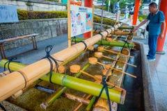 KYOTO JAPAN - JULI 05, 2017: Oidentifierat folk som in tvättar deras händer på handwashpaviljongen i den Fushimi Inari relikskrin Arkivbild