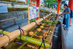 KYOTO JAPAN - JULI 05, 2017: Oidentifierat folk som in tvättar deras händer på handwashpaviljongen i den Fushimi Inari relikskrin Royaltyfria Foton