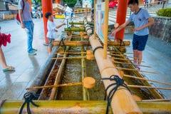 KYOTO JAPAN - JULI 05, 2017: Oidentifierat folk som in tvättar deras händer på handwashpaviljongen i den Fushimi Inari relikskrin Arkivfoto