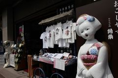 KYOTO, JAPAN - JULY 23 , 2016: Big doll in front of T-shirts are displayed at a souvenir shop. Stock Image