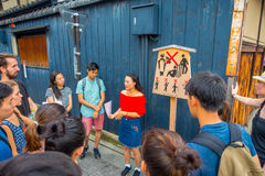 KYOTO, JAPAN - JULY 05, 2017: Crowd of people listening at tourist girl the advice and recomendations to visit in the. City on Gion district in Ky, Japan stock image