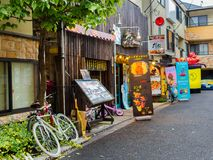 KYOTO, JAPAN - JULY 05, 2017: Row of bikes parked at outdoors of a restaurant, near of a coin machine of juices in Kyoto.  Royalty Free Stock Images