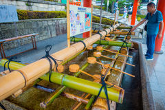 KYOTO, JAPAN - JULY 05, 2017: Unidentified people washing their hands at hand wash pavilion in Fushimi Inari Shrine in Stock Photography
