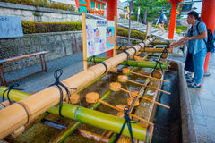 KYOTO, JAPAN - JULY 05, 2017: Unidentified people washing their hands at hand wash pavilion in Fushimi Inari Shrine in Royalty Free Stock Photos