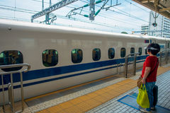 KYOTO, JAPAN - JULY 05, 2017: Unidentified woman admiring the JR700 shinkansen bullet train departing Kyoto station Stock Images