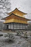 KYOTO, JAPAN - 10. MÄRZ 2014: Altes japanisches goldenes Schloss, Kinkakuji-Tempel (der goldene Pavillon) im Schnee während des W Lizenzfreie Stockbilder