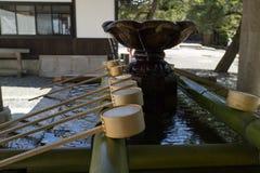 Kyoto, Japan - May 19, 2017: Row of ladles at a purificaton basi royalty free stock images