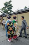 Women wear Japanese kimono on street. Kyoto, Japan - Nov 20, 2016. Japanese women wearing traditional dress Kimono on the historic street in downtown of Kyoto royalty free stock photo
