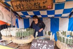 KYOTO, JAPAN - 28 NOV.: Japanse vrouw die geroosterde dango verkopen moc Stock Afbeeldingen