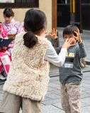 KYOTO, JAPAN - NOVEMBER 7, 2017: Children play in the city street. Close-up. KYOTO, JAPAN - NOVEMBER 7, 2017: Children play in the city street. Close-up royalty free stock image