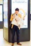 KYOTO, JAPAN - NOVEMBER 7, 2017: Een mens in metro leest nieuws stock foto