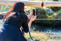 KYOTO, JAPAN - NOVEMBER 7, 2017: The girl takes pictures of the landscape. Close-up. stock photography