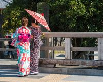KYOTO, JAPAN - NOVEMBER 7, 2017: Girls in a kimono with an umbrella on a city street. Copy space for text. Back view. stock photos