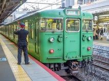 Green old train at Arashiyama station, Japan. KYOTO, JAPAN - NOVEMBER 24 : Green car classic train from Kyoto station stops at Arashiyama train station in Kyoto Royalty Free Stock Image