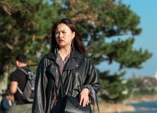 KYOTO, JAPAN - NOVEMBER 7, 2017: Japanese girl in a leather jacket on a background of trees. KYOTO, JAPAN - NOVEMBER 7, 2017: Japanese girl in a leather jacket stock images