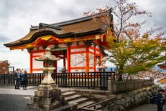 People visiting Kiyomizu-dera buddhist temple - Kyoto, Japan. Kyoto, Japan -November 2, 2018: People visiting in autumn one of the buildings with a thatched roof royalty free stock photo