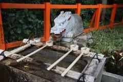 Water purification in Japan. KYOTO, JAPAN - NOVEMBER 28, 2016: Ritual water purification spring of Fushimi Inari Taisha shrine in Kyoto, Japan. There are more Royalty Free Stock Photo