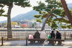 Kyoto, Japan - November 17, 2017: Tourists sitting on benches se. E the beautiful view of Hozu-gawa river during autumn season in Arashiyama, Kyoto, Japan Stock Images