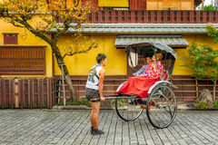 KYOTO, JAPAN - OCTOBER 18, 2016: RICKSHAW RIDE SATISFACTION. Customers took a ride on a rickshaw and arrived at their destination. They were satisfied and Stock Photography