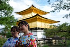 Kyoto Japan - Oktober 01: Okända kvinnliga asiatiska turister poserar framme av den Kinkaku-ji templet på Oktober 01, 2016 i Kyot Fotografering för Bildbyråer