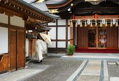 Japanese monk in white dress from behind on outdoors in temple Kyoto royalty free stock photo