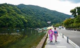 Kyoto, Japonia - 24 2016 Lipiec Dwa kobiety ubierającej w gejszie chodzą Katsura rzeką w Arashiyama terenie Kyoto, Japonia fotografia stock