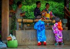 KYOTO JAPONIA, LIPIEC, - 05, 2017: Młodzi japończycy jest ubranym tradycyjnego kimono i trzyma parasole w ich rękach wewnątrz Obrazy Royalty Free